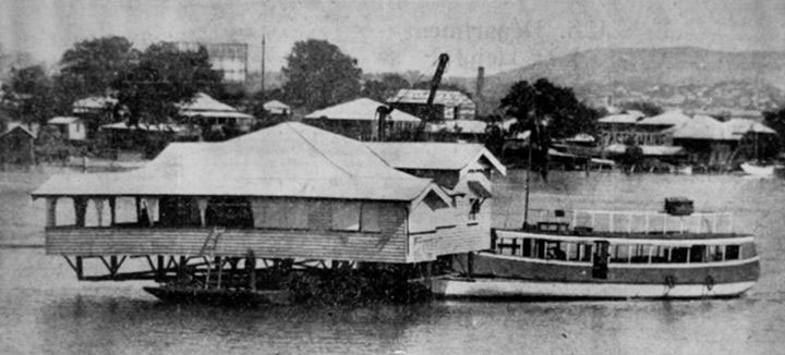 house being pushed by a tug boat down the Brisbane River